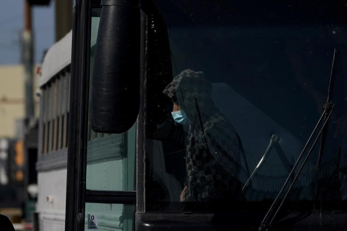 """A migrant wears a face mask to protect against COVID-19 while walking off a U.S. Customs and Border Protection bus at the McAllen-Hidalgo International Bridge as he is deported to Mexico, Saturday, March 20, 2021, in Hidalgo, Texas. The fate of thousands of migrant families who have recently arrived at the Mexico border is being decided by a mysterious new system under President Joe Biden. U.S. authorities are releasing migrants with """"acute vulnerabilities"""" and allowing them to pursue asylum. But it's not clear why some are considered vulnerable and not others. (AP Photo/Julio Cortez)"""