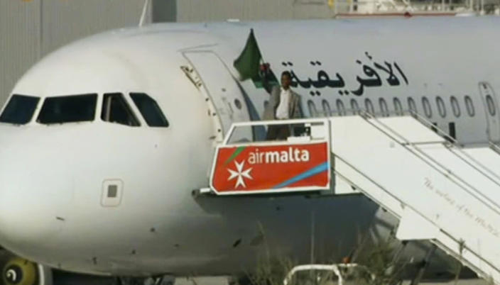 <p> An Afriqiyah Airways plane stands on the tarmac at Malta International airport as an unidentified man waves a flag, Friday, Dec. 23, 2016. Hijackers diverted the Libyan commercial plane to Malta on Friday and threatened to blow it up with hand grenades, Maltese authorities and state media said. (TVM via AP) </p>