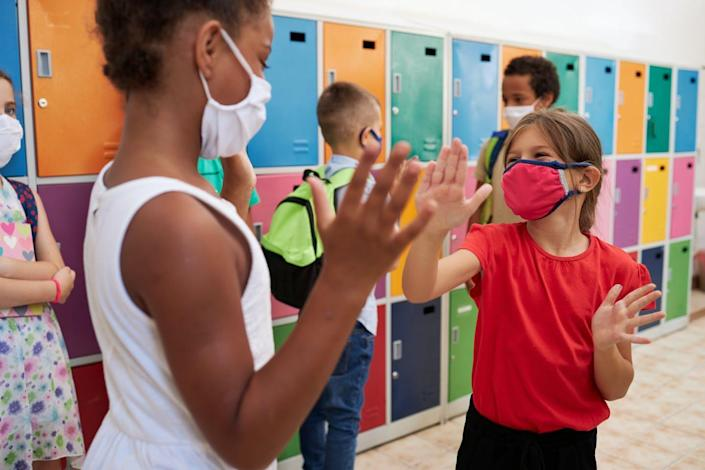 Two school girls wearing masks play together in a classroom.