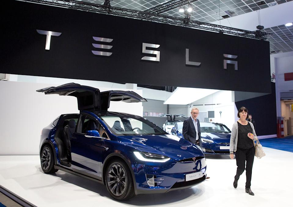 A couple walk next to the new Tesla Model X during the opening of the Brussels Auto Show in Brussels, Friday, Jan. 18, 2019. (AP Photo/Virginia Mayo)