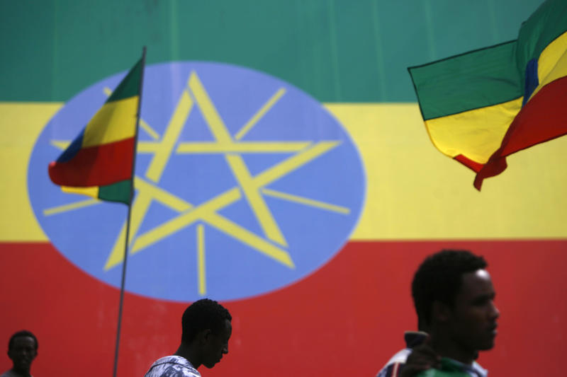 People walk in front of Ethiopian flags in Addis Ababa, Ethiopia on September 10, 2007