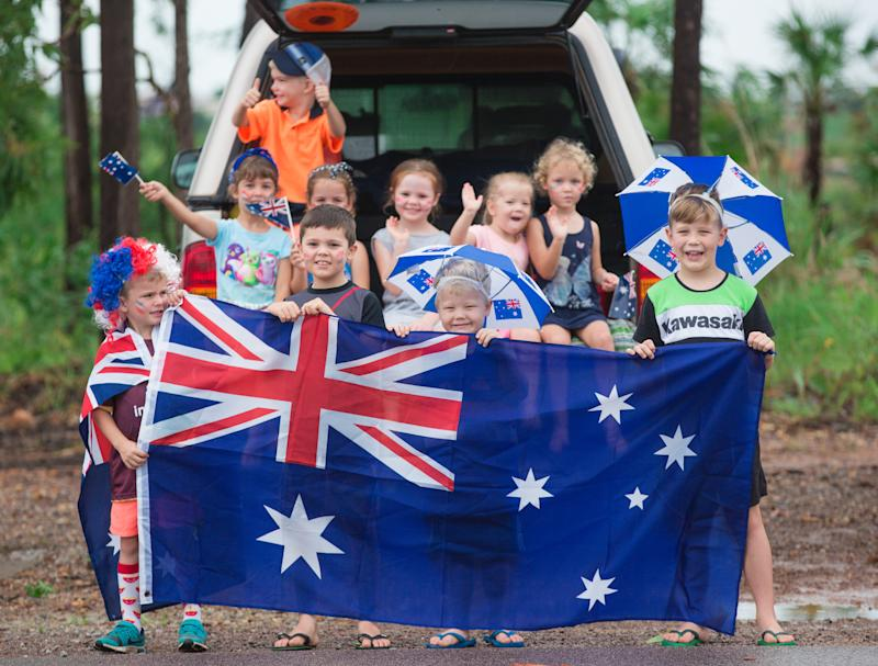 Participants are seen along the parade route during Australia Day Ute Run in Darwin.