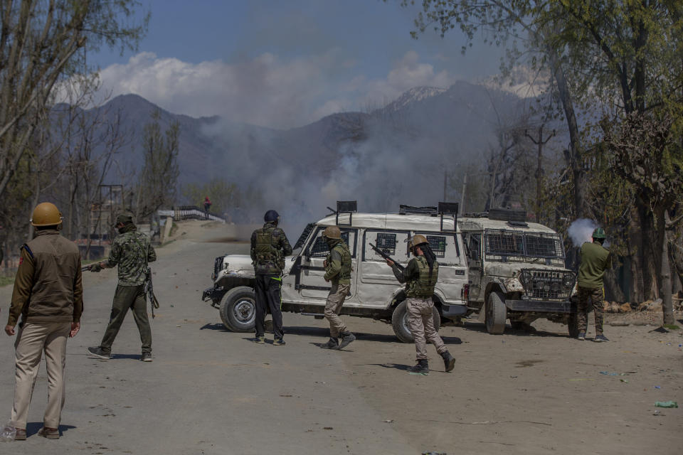 Indian policemen fire pellets and teargas shells at Kashmiri villagers as they throw stones and bricks at them during a protest near the site of a gunbattle in Pulwama, south of Srinagar, Indian controlled Kashmir, Friday, April 2, 2021. Anti-India protests and clashes have erupted between government forces and locals who thronged a village in disputed Kashmir following a gunbattle that killed three suspected militants. Police say the gunfight on Friday erupted shortly after scores of counterinsurgency police and soldiers launched an operation based on tip about presence of militants in a village in southern Pulwama district. (AP Photo/ Dar Yasin)