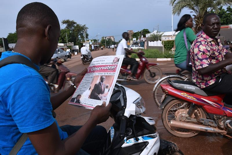 A man reads on his motorbike a newspaper bearing a picture of Burkina Faso's interim president Michel Kafando on the frontpage on September 25, 2015 in Ouagadougou (AFP Photo/Sia Kambou)