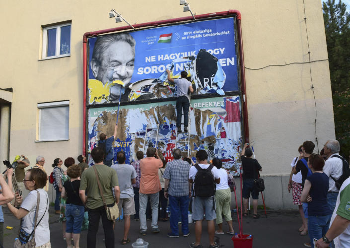 FILE - In this Wednesday, July 12, 2017 file photo, activists from the Egyutt (Together) party tear down an advertisement from the Hungarian government against George Soros in Budapest, on the day it said it would soon end its disputed ad campaign against the Hungarian-American billionaire. The billboards, posters and TV ads have been criticized by Hungarian Jewish leaders and others for their anti-Semitic overtones. (AP Photo/Pablo Gorondi)