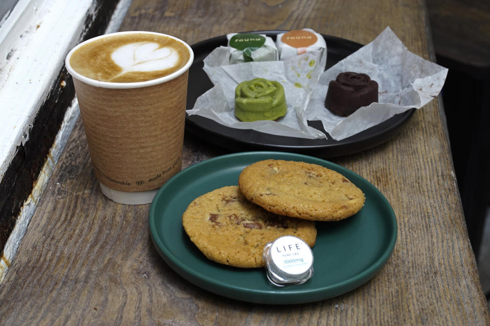 Coffee, biscuits, green tea and chocolate mooncake that contain cannabidiol, or CBD, a substance from the cannabis plant, are displayed at the Found Cafe in Hong Kong on Sept. 13, 2020. Cannabis, also known as marijuana, in Hong Kong may be illegal, but the new Found Cafe is offering a range of food and drinks that contain parts of the cannabis plant without breaking any local laws. (AP Photo/Vincent Yu)