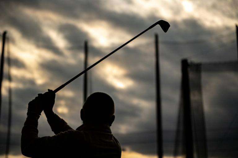 Hiroyuki Yamaya, a company CEO, practices his swing at a golf club in the Setagaya district of Tokyo