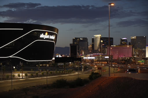 """FILE - In this July 22, 2020, file photo, the sun sets behind Allegiant Stadium, new home of the Las Vegas Raiders football team, as it nears completion in Las Vegas. Officials in Nevada have declared """"substantial completion"""" after nearly 1,000 days of construction of the $2 billion Allegiant Stadium in Las Vegas designed to be the home of the NFL's relocated Raiders. (AP Photo/John Locher, File)"""