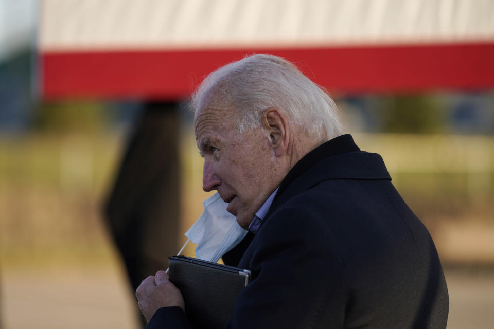 Democratic presidential candidate former Vice President Joe Biden puts on a face mask during a rally at the Minnesota State Fairgrounds in St. Paul, Minn., Friday, Oct. 30, 2020. (AP Photo/Andrew Harnik)