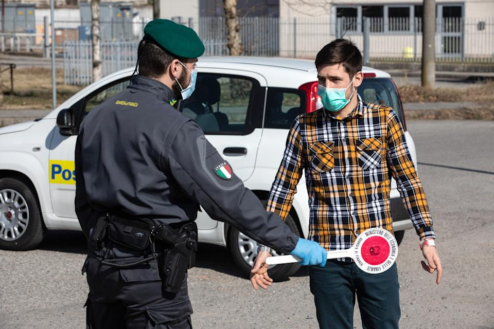 CASALPUSTERLENGO, ITALY - FEBRUARY 24: An Italian Guardia di Finanza (Custom Police) officer, wearing a respiratory mask, talks to a young man at a road block on February 24, 2020 in Casalpusterlengo, south-west Milan, Italy. Casalpusterlengo is one of the ten small towns placed under lockdown after coronavirus sparked infections throughout the Lombardy region. Italy is the last country to be hit hard by the virus with five dead and more than 224 infected as of today. The spread marks Europe's biggest outbreak, prompting Italian Government to issue draconian safety measures. (Photo by Emanuele Cremaschi/Getty Images)
