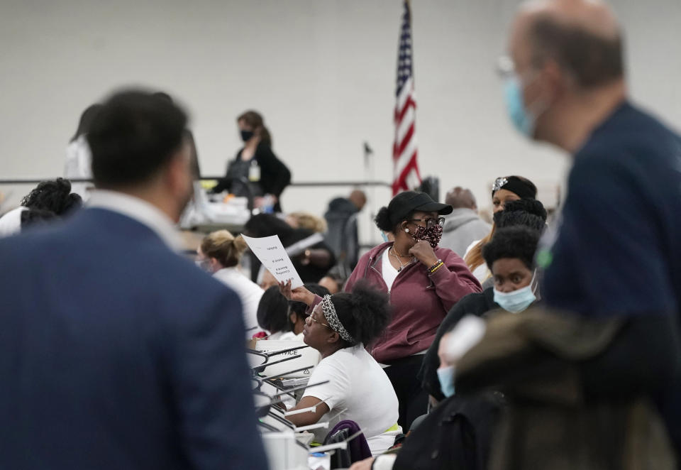Election challengers observe as ballots are counted at the central counting board, Wednesday, Nov. 4, 2020, in Detroit. (AP Photo/Carlos Osorio)