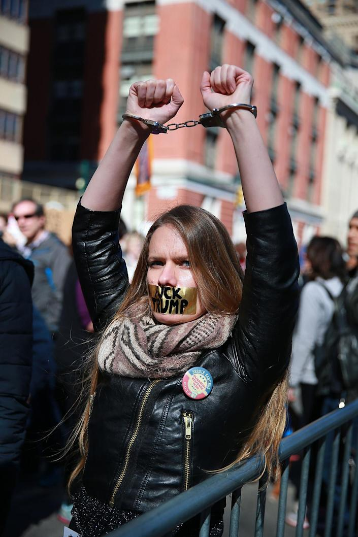 """<p>A young woman wears handcuffs and has her mouth taped shut with the words """"F*** TRUMP"""" inside police barricades at the """"Not My President's Day"""" rally at Central Park West in New York City on Feb. 20, 2017. (Gordon Donovan/Yahoo News) </p>"""