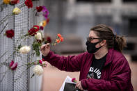 Flowers were placed on the fence in front of the Hennepin County Government Center by Stacey Bornholdt one day before jury selection is set to begin in the trial of former Minneapolis officer Derek Chauvin, who is accused of killing George Floyd Sunday, March 7, 2021, in Minneapolis, Minn. (Jerry Holt /Star Tribune via AP)
