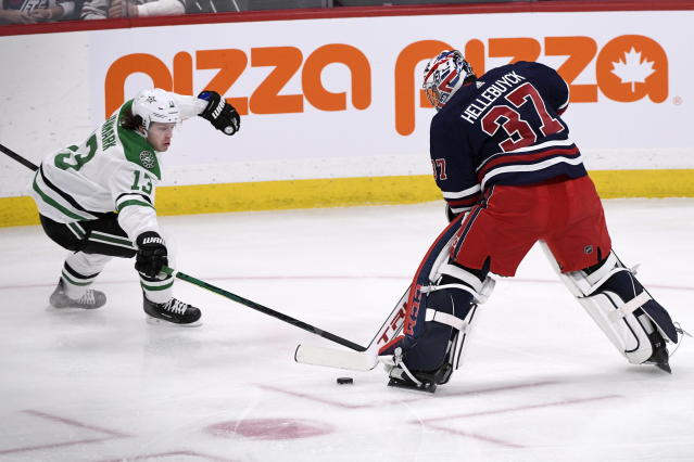 Winnipeg Jets' goaltender Connor Hellebuyck (37) plays the puck out of his crease as Dallas Stars' Mattias Janmark (13) skates toward him during the first period of an NHL hockey game, Tuesday, Dec. 3, 2019 in Winnipeg, Manitoba. (Fred Greenslade/The Canadian Press via AP)