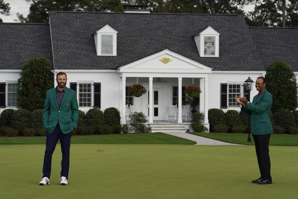 Tiger Woods, right, applauds as Masters golf champion Dustin Johnson poses in his green jacket following his victory Sunday, Nov. 15, 2020, in Augusta, Ga. (AP Photo/Chris Carlson)