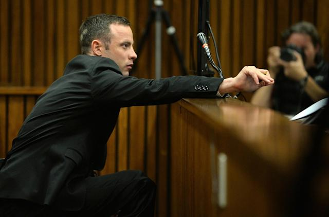 Oscar Pistorius, leans forward in the dock in court in Pretoria, South Africa, Friday, March 14, 2014 on the tenth day of proceedings. Pistorius is charged with the shooting death of his girlfriend Reeva Steenkamp, on Valentines Day in 2013. (AP Photo/Phill Magakoe, Pool)