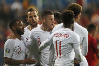 England players hug teammate Ross Barkley, center, after he scored his side's third goal during the Euro 2020 group A qualifying soccer match between Montenegro and England at the City Stadium in Podgorica, Montenegro, Monday, March 25, 2019. (AP Photo/Darko Vojinovic)