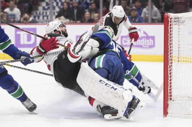 New Jersey Devils' Kyle Palmieri, left, crashes into Vancouver Canucks goalie Jacob Markstrom, of Sweden, as New Jersey's Wayne Simmonds, back right, scores during the first period of an NHL hockey game in Vancouver, British Columbia, Sunday, Nov. 10, 2019. (Darryl Dyck/The Canadian Press via AP)