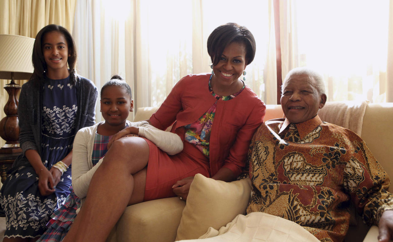 In this photo provided by the Nelson Mandel Foundation on Tuesday, June 21, 2011, US First Lady Michelle Obama centre, accompanied by her daughters, Malia, left and Sasha, meet former South African President Nelson Mandela, at this home, in Houghton, South Africa. First lady Michelle Obama and her family met with Nelson Mandela during a private visit at the former South African president's home. Mrs. Obama, daughters Malia and Sasha, and her mother, Marian Robinson, were viewing some of Mandela's personal papers at his foundation Tuesday when according to White House officials, he sent word that he wanted to meet them. It was Mrs. Obama's first meeting with the prisoner-turned-president. (AP Photo/ Debbie Yazbek, Nelson Mandela Foundation) EDITORIAL USE ONLY