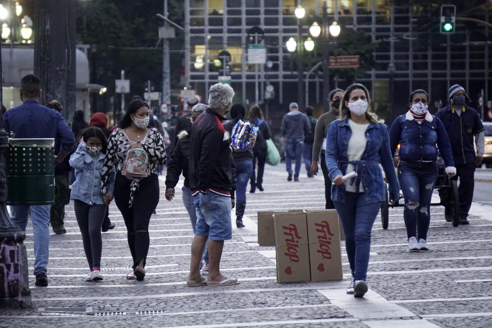 People wearing a face mask walk in Sao Paulo, Brazil, on July 20, 2021 amid the Covid-19 pandemic. (Photo by Cris Faga/NurPhoto via Getty Images)