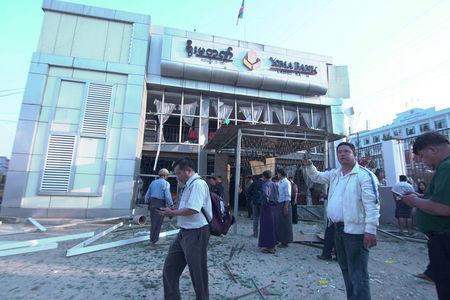 People inspect the damage at a bank after a bomb blast, in Lashio, Myanmar February 21, 2018 in this picture obtained from social media. Ministry of Information Webportal Myanmar/via REUTERS