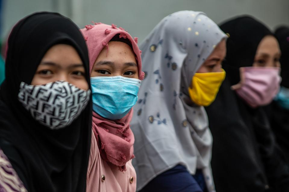 Filipino Muslims wear masks as a protective measure against the spread of covid-19 as they gather along the street outside the mosque during Eid'l Adha on July 31, 2020 in Manila, Philippines.(Photo by Lisa Marie David/NurPhoto via Getty Images)