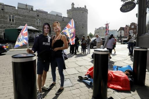 A couple wearing masks of Britain's Prince Harry and US actress Meghan Markle pose with Union flags near Windsor Castle on May 18, 2018, the day before the Royal wedding