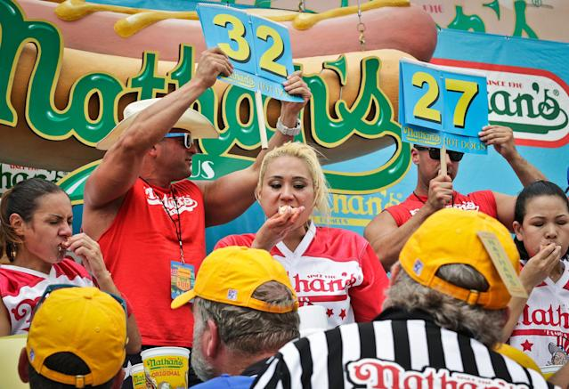<p>Miki Sudo, center, competes in the women's division of the Nathan's Famous Hot Dog Eating Contest on Tuesday, July 4, 2017, in New York. The Las Vegas woman ate 41 hot dogs and buns in 10 minutes to win her fourth straight title. (AP Photo/Bebeto Matthews) </p>