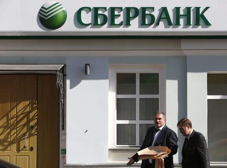Men walk past an office of Sberbank in Moscow