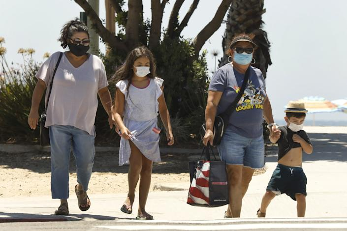 "The Sanchez family, of Los Angeles, wear their masks while visiting Laguna Beach on Friday, July 31, 2020. In Laguna Beach. <span class=""copyright"">(Carolyn Cole/Los Angeles Times)</span>"