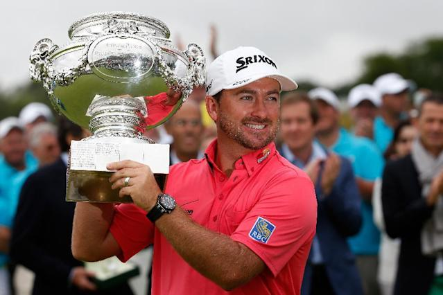 Northern Ireland's golfer Graeme McDowell poses with his trophy after winning the 2014 Alstom Open de France on July 6, 2014 at Le Golf National in Guyancourt, near Paris (AFP Photo/Thomas Samson)