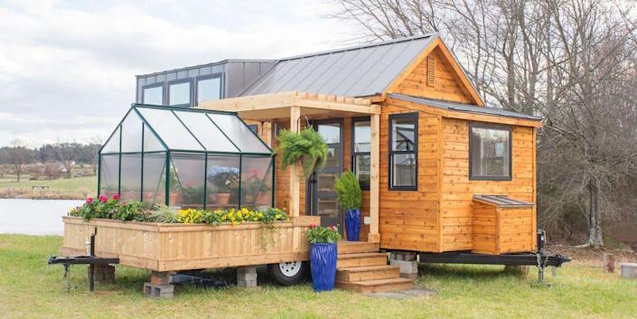 """<p> With an attachable greenhouse and porch, the Elsa by Olive Nest Tiny Homes proves that you can still have it all in a small space.</p><p><a class=""""link rapid-noclick-resp"""" href=""""https://tinyhouselistings.com/listings/taylors-sc-12-the-elsa/"""" rel=""""nofollow noopener"""" target=""""_blank"""" data-ylk=""""slk:SHOP NOW"""">SHOP NOW</a> <a class=""""link rapid-noclick-resp"""" href=""""https://www.countryliving.com/home-design/house-tours/news/a45229/greenhouse-tiny-home/"""" rel=""""nofollow noopener"""" target=""""_blank"""" data-ylk=""""slk:SEE INSIDE"""">SEE INSIDE</a> </p>"""