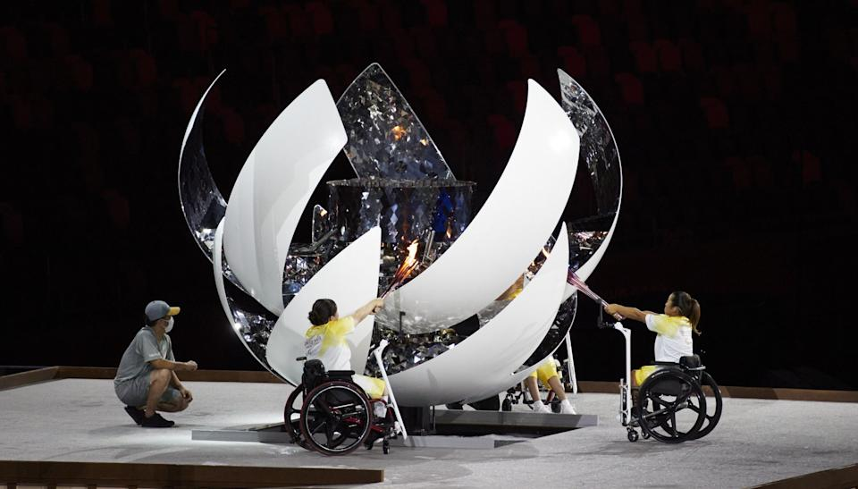 Three Japanese athletes light the flame as the Paralympics begin with an opening ceremony in Tokyo