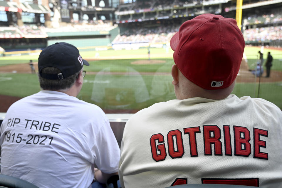 Chuck Hanus, left, from Orlando Fla., and Michael Bell, from Las Vegas, watch a baseball game between the Cleveland Indians and the Texas Rangers in Arlington Texas, Sunday, Oct. 3, 2021. Both men flew to Texas for the final Indians game before the team's name change. (AP Photo/Matt Strasen)