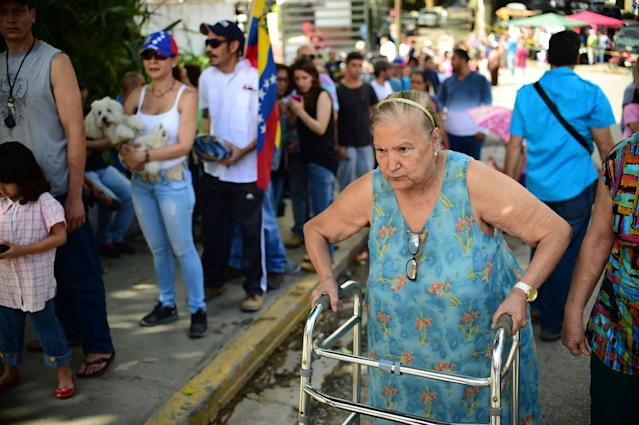 <p>A woman with a walker heads to a polling station as others queue in Caracas on July 16, 2017 during an opposition-organized vote to measure public support for President Nicolas Maduro's plan to rewrite the constitution. (Ronaldo Schemidt/AFP/Getty Images) </p>
