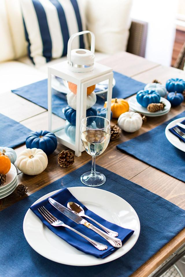 """<p>Blue may not seem the obvious first choice when it comes to selecting a color scheme for your Thanksgiving dinner. But here, helped along by obvious autumnal touches (gourds, pinecones, and a vintage-inspired lantern), it makes perfect sense—and it's creative and interesting to boot.</p><p><strong>Get the tutorial at <a href=""""https://www.itallstartedwithpaint.com/thanksgiving-table-setting-turkey-talk/"""" target=""""_blank"""">It All Started with Paint</a>.</strong><br></p><p><strong><a class=""""body-btn-link"""" href=""""https://www.amazon.com/Utopia-Kitchen-Cotton-Dinner-Napkins/dp/B00L1HZD5I?tag=syn-yahoo-20&ascsubtag=%5Bartid%7C10050.g.634%5Bsrc%7Cyahoo-us"""" target=""""_blank"""">SHOP BLUE NAPKINS</a><br></strong></p>"""