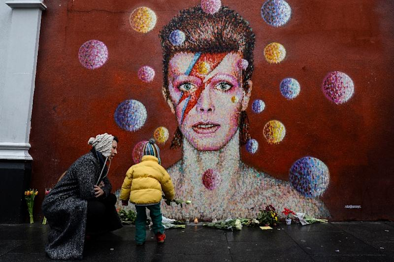 Floral tributes are left beneath a mural of British singer David Bowie, painted by Australian street artist James Cochran, aka Jimmy C, following the announcement of Bowie's death, in Brixton, south London, on January 11, 2016 (AFP Photo/Chris Ratcliffe)