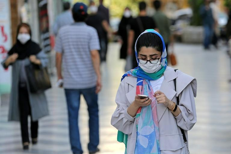 Shoppers, wearing protective masks due to the Covid-19 pandemic, walk past shops in Vali-asr Square in the Iranian capital Tehran