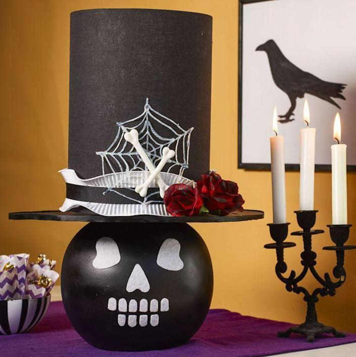 """<p>Make this simple and festive lamp by attaching a felt face to the lamp base and a black cardboard brim to a tall shade.</p><p><strong>1. </strong>Spray paint round table lamp black; let dry. Cut facial features from white adhesive felt and press in place.</p><p><strong>2. </strong>For top hat, start with a black drum lampshade. Cut a circle of black foam core that's <span>4 inches</span> wider than shade on all sides for a brim; cover outer edge with ¼-inch-wide black ribbon. Cut a center hole for harp, then hot-glue brim to bottom of shade and attach to lamp.</p><p><strong>3. </strong>To make spiderweb, squeeze white dimensional paint onto wax paper in web shape; once dry, peel off.</p><p><strong>4. </strong>Hot-glue ribbon, spiderweb, faux red roses brushed with black paint, and small bones to hat.</p><p><strong>What You'll Need: </strong><a href=""""http://www.lampsplus.com/products/riverceramic-bristol-gloss-white-table-lamp__13v12.html"""" rel=""""nofollow noopener"""" target=""""_blank"""" data-ylk=""""slk:Bristol table lamp"""" class=""""link rapid-noclick-resp"""">Bristol table lamp</a> ($148, Lamps Plus)</p>"""