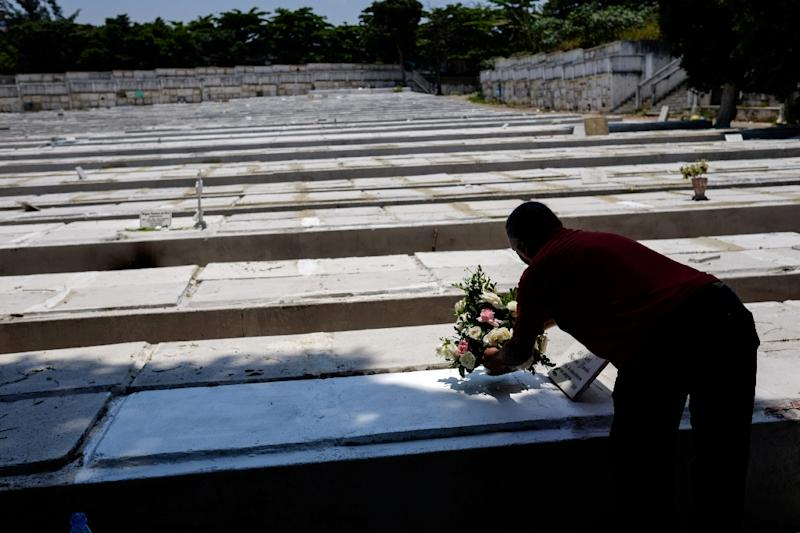 A man puts flowers at his stillborn daughter's tomb in Rio de Janeiro, Brazil, on November 2, 2014