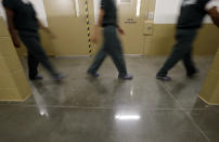 Inmates walk down a hallway at the Otay Mesa Detention Center Wednesday, Aug. 23, 2017, in San Diego. The facility was at the center of the first big novel coronavirus outbreak at a U.S. immigration detention center in April 2020. (AP Photo/Gregory Bull)