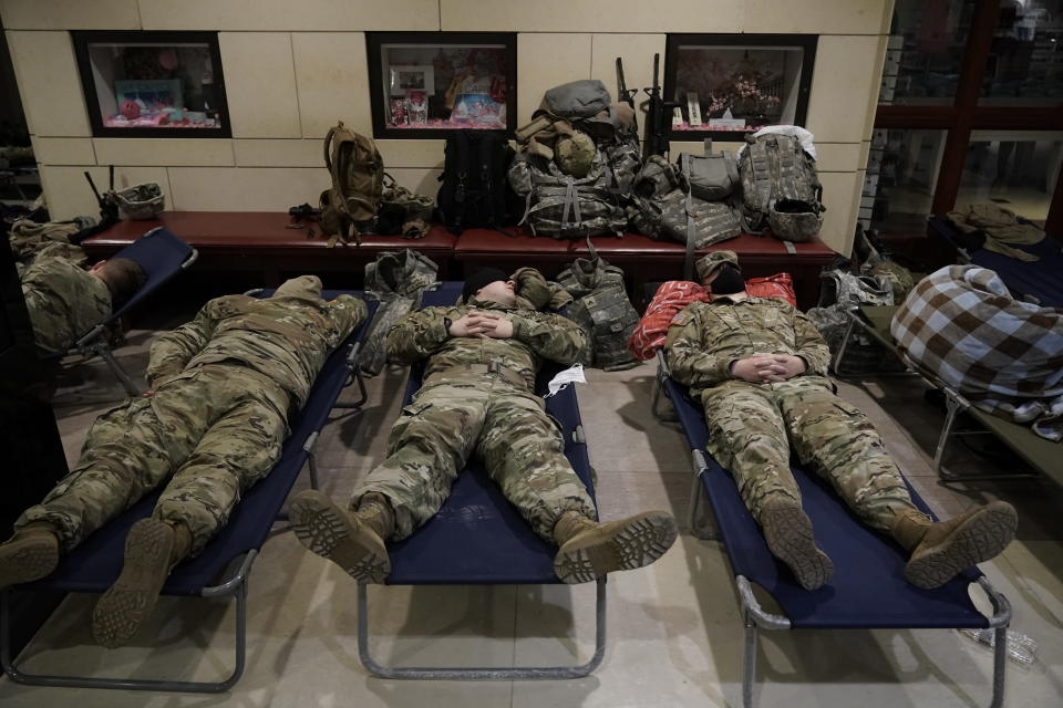FILE - In this Jan. 18, 2021, file photo National Guard troops sleep inside the Capitol Visitor's Center at the Capitol in Washington. Over the past year, National Guard members have been called in to battle the COVID-19 pandemic, natural disasters and race riots. (AP Photo/J. Scott Applewhite, File)