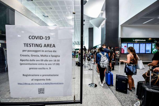 PHOTO: Passengers arriving from four Mediterranean countries at Italy's Milan Malpensa Airport wait in a line to be tested for COVID-19 on Aug. 20, 2020. (Claudio Furlan/AP)