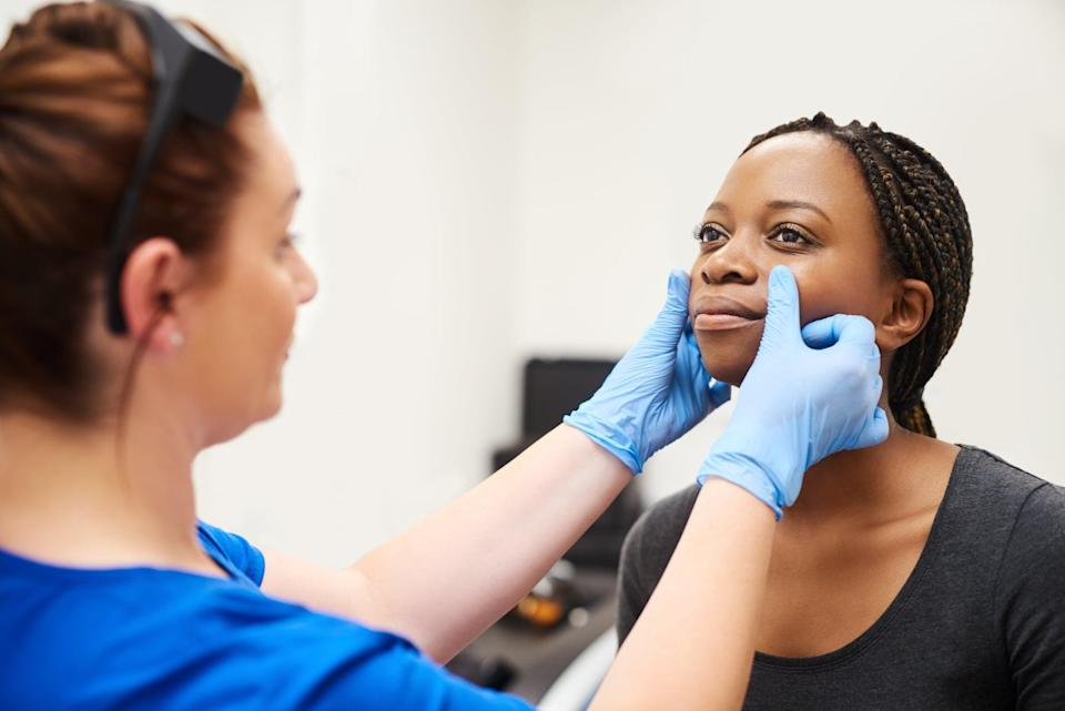 Shot of a beautiful young woman getting her face analyzed by a nurse at a beauty clinic