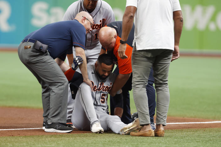 Detroit Tigers' Derek Hill lays is helped up off the field during the fifth inning of a baseball game against the Tampa Bay Ray Saturday, Sept. 18, 2021, in St. Petersburg, Fla. (AP Photo/Scott Audette)
