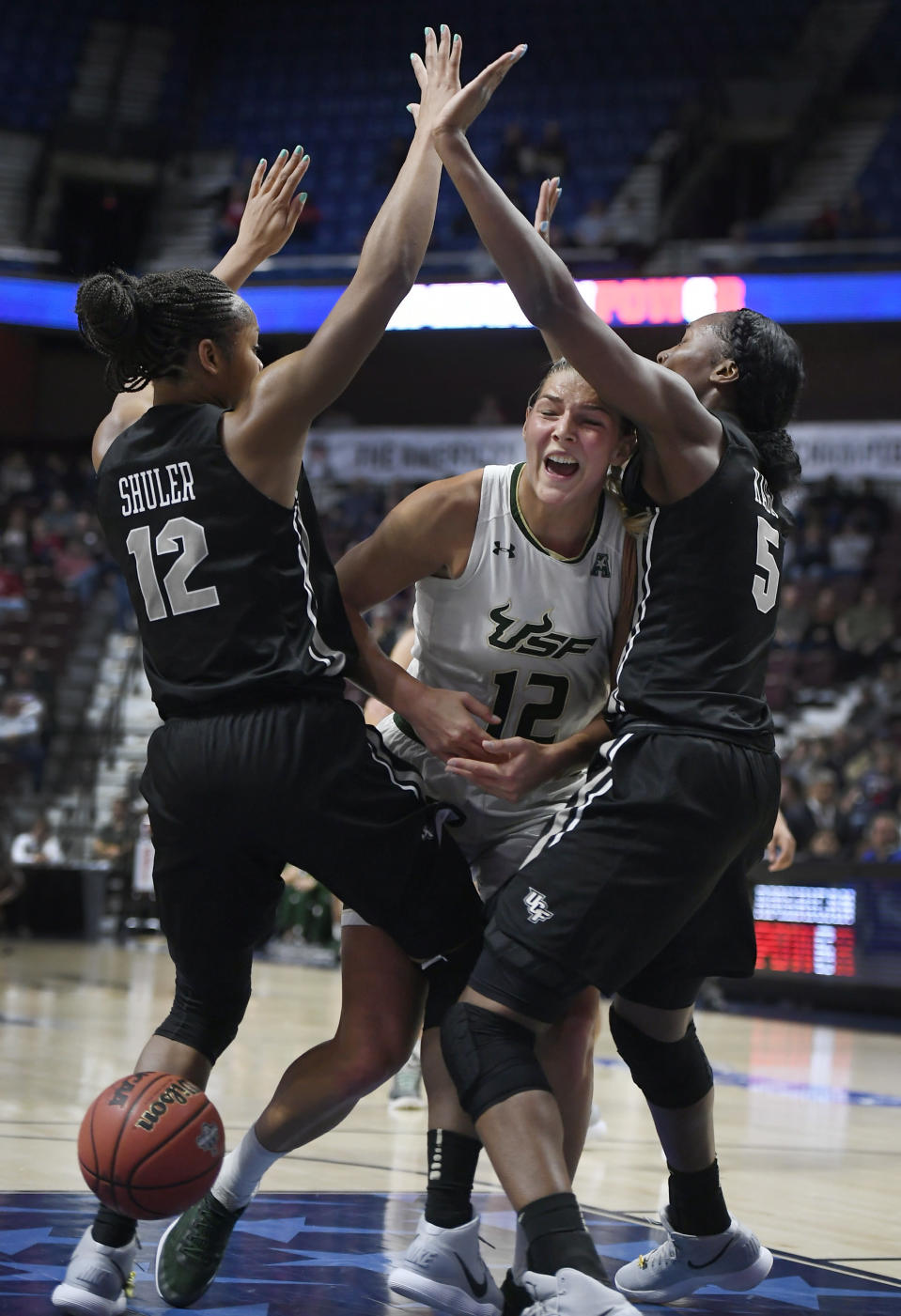 South Florida's Maria Jespersen, center, looses the ball under pressure from Central Florida's Nyala Shuler , left, and Masseny Kaba , right, during the first half of an NCAA college basketball game in the American Athletic Conference tournament semifinals at Mohegan Sun Arena, Monday, March 5, 2018, in Uncasville, Conn. (AP Photo/Jessica Hill)
