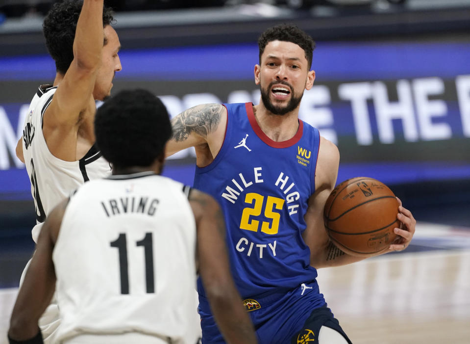 Denver Nuggets guard Austin Rivers, right, drives as Brooklyn Nets guards Landry Shamet, back left, and Kyrie Irving defend during the first half of an NBA basketball game Saturday, May 8, 2021, in Denver. (AP Photo/David Zalubowski)