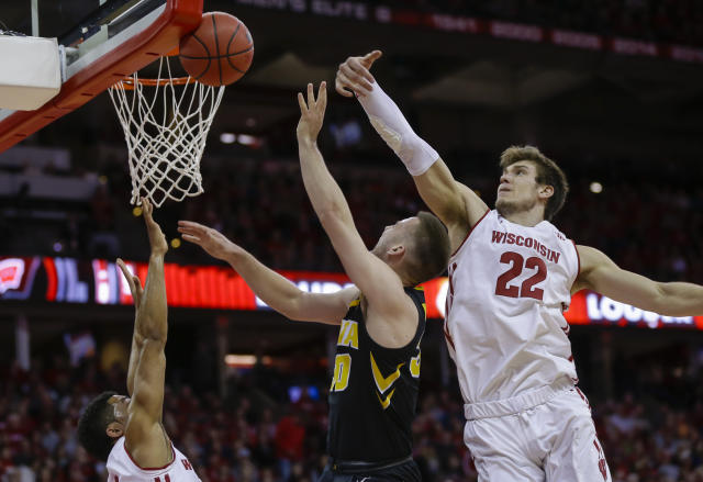 Wisconsin's Ethan Happ (22) blocks a shot by Iowa's Connor McCaffery (30) as Wisconsin's D'Mitrik Trice, left, defends during the first half of an NCAA college basketball game Thursday, March 7, 2019, in Madison, Wis. (AP Photo/Andy Manis)