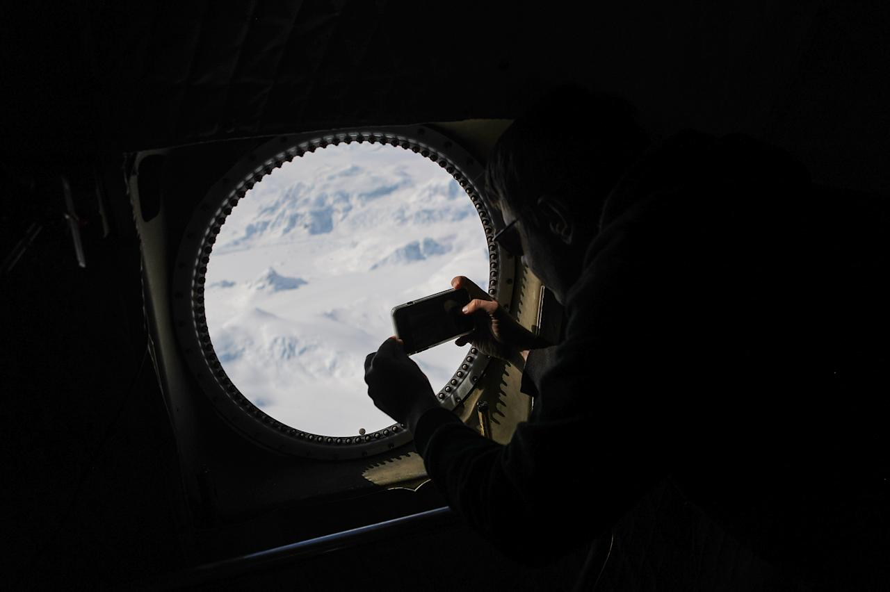 <p>NASA Operation IceBridge project scientist Nathan Kurtz photographs from NASA's research aircraft in the Antarctic Peninsula region on Nov. 3, 2017, above Antarctica. (Photo: Mario Tama/Getty Images) </p>
