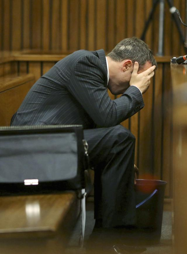 Oscar Pistorius covers his head as he reaches for a bucket on the floor nearby, as he listens to cross questioning about the events surrounding the shooting death of his girlfriend Reeva Steenkamp, in court during his trial in Pretoria, South Africa, Monday, March 10, 2014. Pistorius vomited in the dock at his murder trial Monday as he heard graphic details in testimony from pathologist Prof. Gert Saaymanof, of the injuries sustained by the girlfriend he fatally shot. Pistorius is charged with the shooting death of his girlfriend Steenkamp, on Valentines Day in 2013. (AP Photo/Siphiwe Sibeko, Pool)